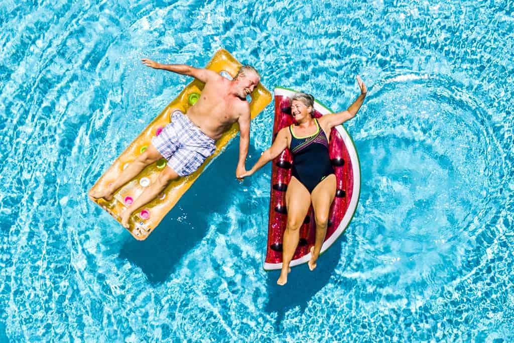 older couple on pool floats